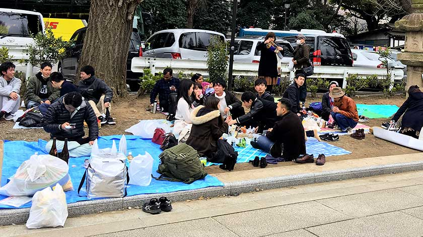 A typical hanami party sitting on a tarpaulin